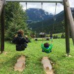 Auf dem Bild ist eine Erwachsene und ein Kind nebeneinander auf einer Schaukel zu sehen. Die Schaukel befindet sich in grüner Umgebung auf einem Berg.