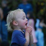 Auf dem Bild ist ein Kind, das vermutlich gerade ein Konzert anhört.