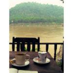 """Am Bild ist ein Tisch zu sehen, der an einem Fluss steht und auf dem eine Kaffeetasse zu sehen ist. Der Titel ist """"Der Perfekte Reiseschreibtisch"""""""