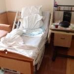 zu sehen ist ein leeres Bett in einem Krankenhauszimmer