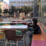 Ein Kind sitz mit Kopfhörern und einem Eis in der Hand in einem Gastgarten.