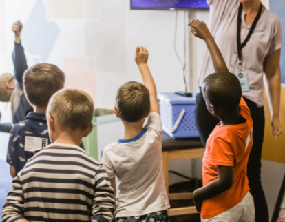 Kinder, die die Hand hochstrecken, um in der Schule dranzukommen.