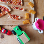 Essstisch mit einem Brett auf dem eine angeschnittene Pizza steht, ein Kinder Trinkbecher und einige Spielzeugautos.