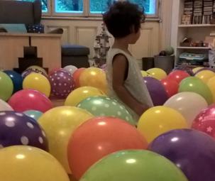 Kind sitzt in einem bunten Luftballongberg am Boden